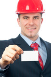 Handsome smiling engineer with hard hat showing business card