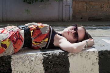 the beautiful girl lies on a concrete plate