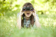 Teen girl with binocular at green grass