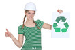 Female construction worker with a recycle sign
