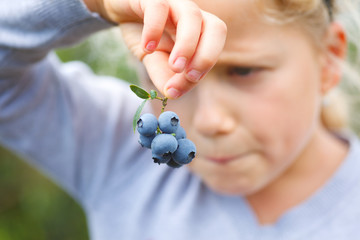 girl holding blueberries
