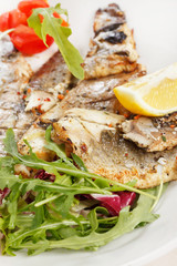 Grilled fish fillet with tomato and lemon
