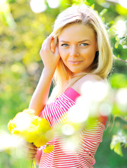 Beautiful woman with flowers in a park