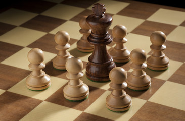 Chess pawns around the king