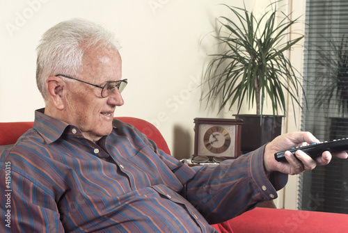 old man with television remote control