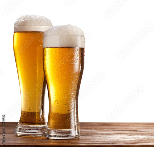 Two glasses of beers on a wooden table.