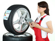 Female motor mechanic checks tire label with touchpad