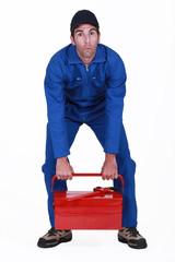 Man struggling to lift tool box