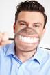 Mann mit Lupe vor Mund