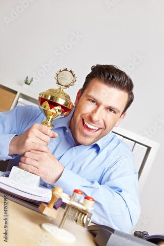 Jubelnder Geschäftsmann mit Pokal