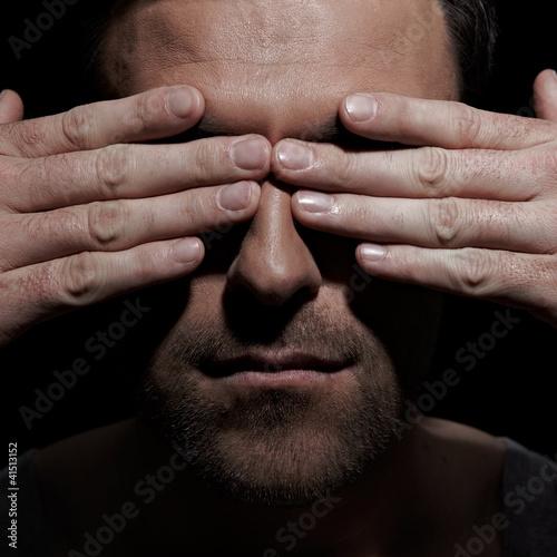 Mann verdeckt sein Gesicht