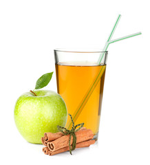 Apple juice in a glass, green apple and cinnamon sticks
