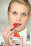 Blond woman eating strawberries