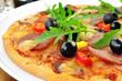 Pizza mit schwarzen Oliven und Rucola