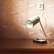 Old-fashioned desk lamp on the desk near the wall