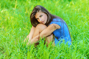 Portrait of young beautiful woman sitting on grass