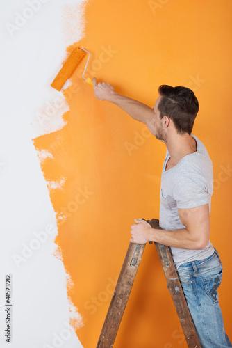 mann streicht eine wand mit farbrolle