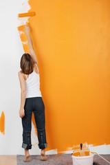 frau streicht eine wand orange