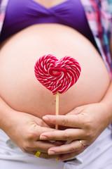 Mulher grávida com pirulito coração