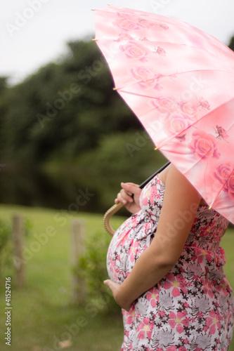 Mulher grávida com sombrinha rosa