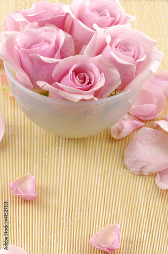 Pink rose flowers floating in a bowl with water and petal