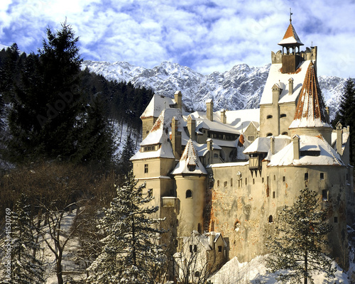 Dracula's Bran Castle in winter with snow and mountains.