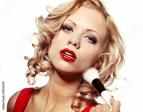 Beautiful blond woman applying makeup on her face