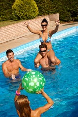 Happy people playing in swimming pool
