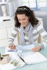Young woman checking bills