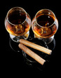 two glasses of brandy and cigars on black background