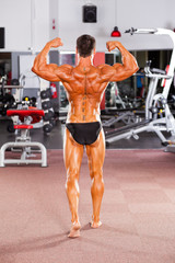 rear view of male bodybuilder posing in gym