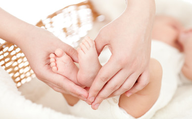 parent's hands keeping newborn baby's feet