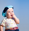 Curious amusing little baby boy in a beret with a finger in to t