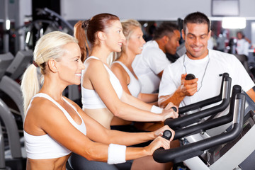 professional gym trainer monitoring trainees cycling performance