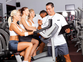 sport coach timing cyclist on gym bike