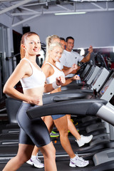 group of fitness people running on treadmill in gym
