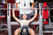 fitness woman lifting barbell in gym with trainer's help