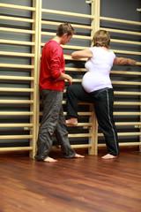 pregnant woman + child birth instructor at gym ladder