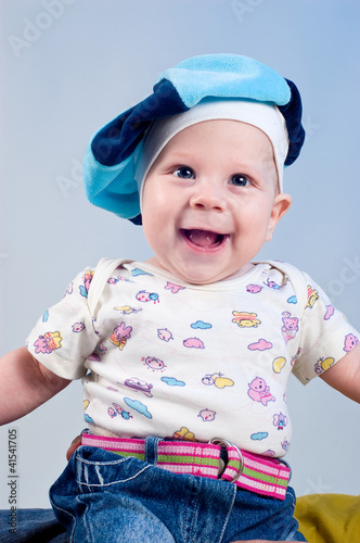 Amusing baby boy in a beret in a studio on a dark blue backgroun