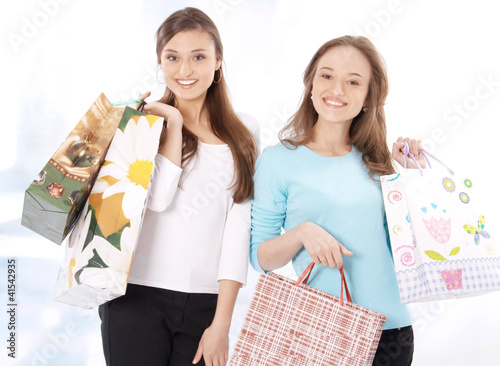 Portrait of stunning young women carrying shopping bags