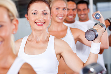group of fitness people lifting weight in gym