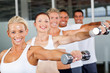 group of people working out with dumbbells in gym