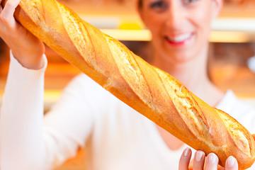 Bäckerin in ihrer Bäckerei verkauft Brot Baguette