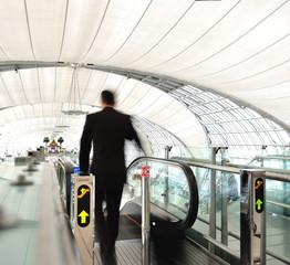 Businees man go down escaltor at airport
