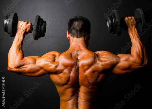 rear view of bodybuilder training with dumbbells - 41546590