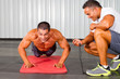 fitness man and personal trainer in gym doing push-ups