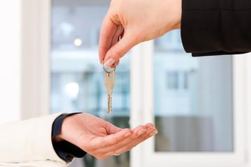 Junge Maklerin übergibt die Schlüssel in einer Wohnung