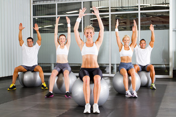 group of fitness people exercise on gymnastic balls in a gym