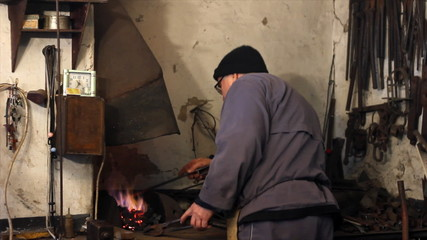 Blacksmith at work, melting iron in a small furnace