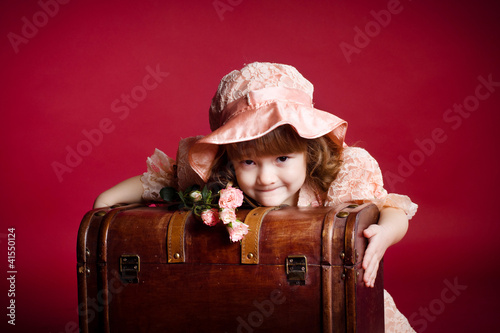 A beautiful young girl holding wooden treasure trunk and roses